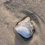 Stone and depression in sand