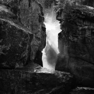 black and white of cleft in rock with sun pouring through it
